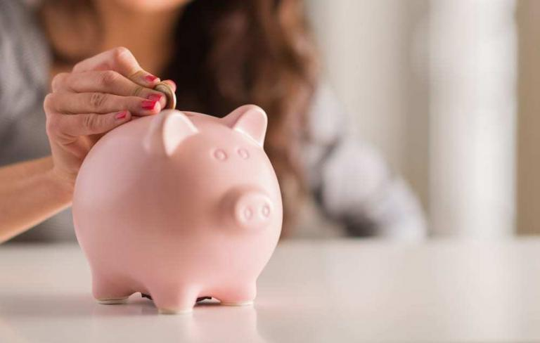 Close-up of woman putting coin in piggy bank