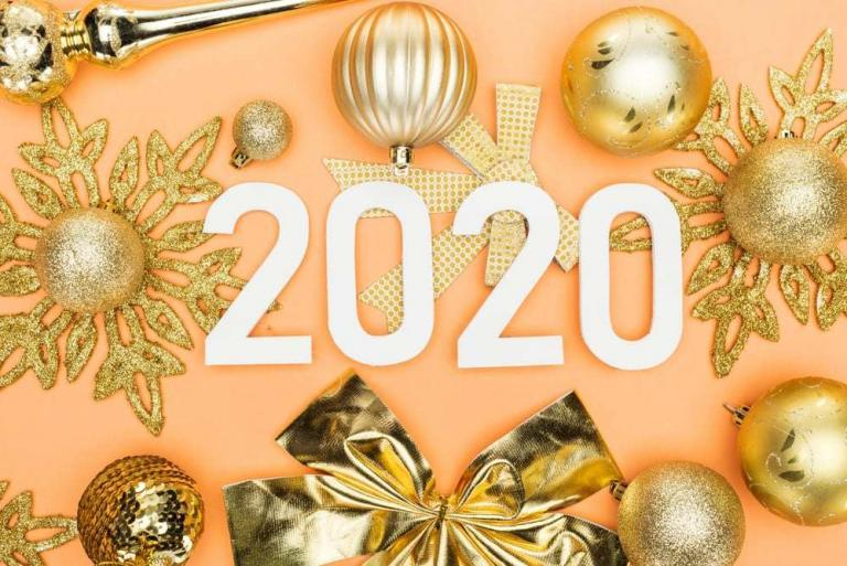 2020 on yellow background, surrounded by gold snowflakes, ornaments, and bows