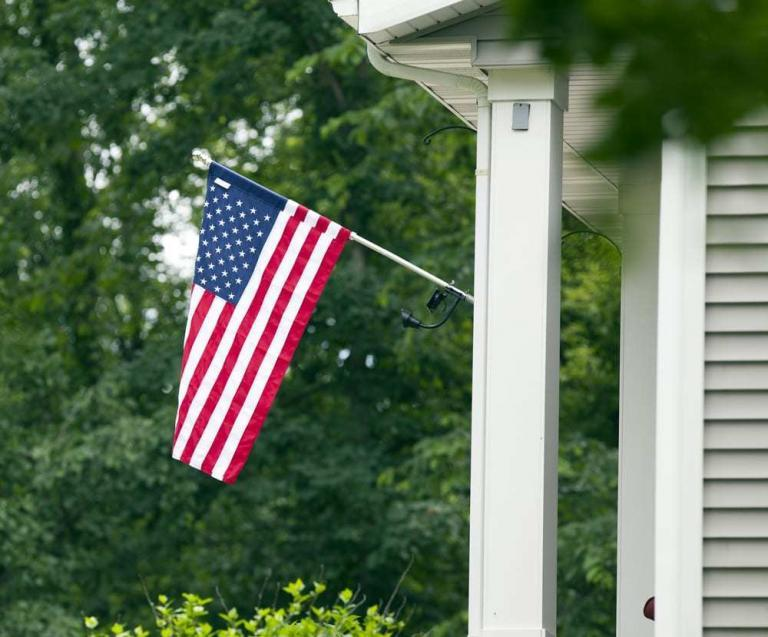 Close-up of American flag hanging on a house exterior