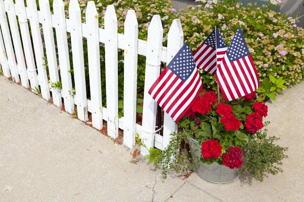 american flags in a flower pot beside white fence
