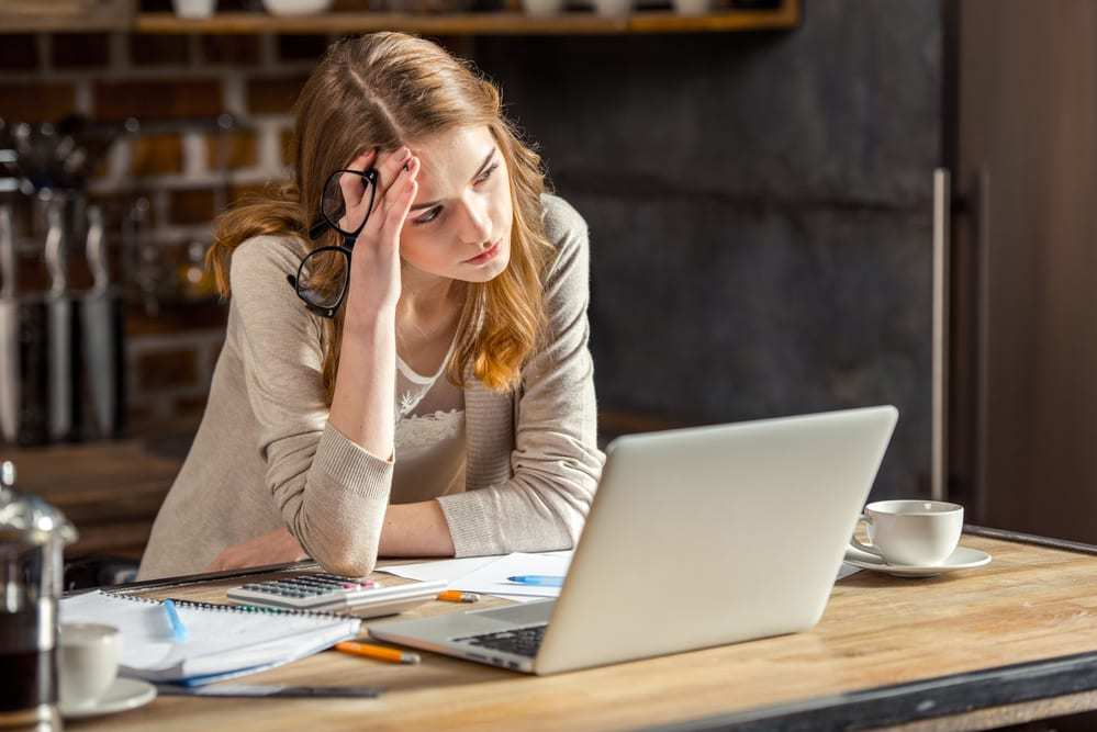 Pensive young woman looking at laptop, notes beside her