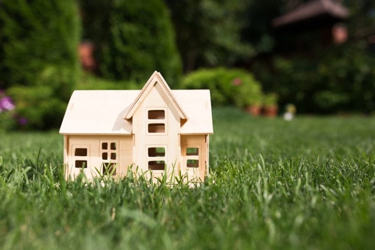 Wooden house model sitting in grass