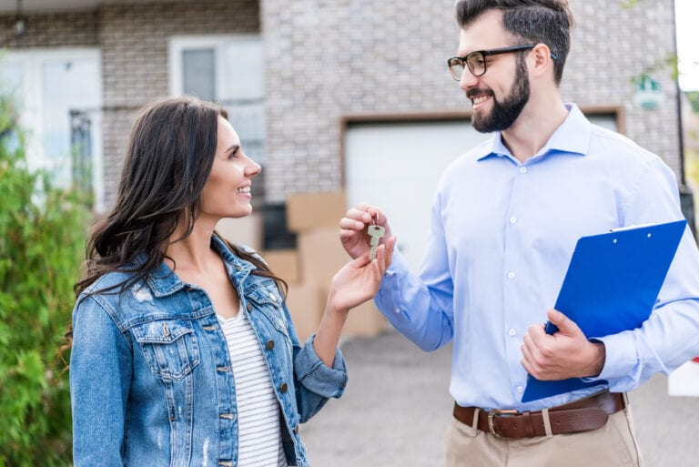 Young woman receiving house keys from real estate agent