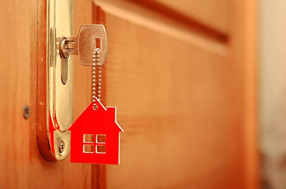 house key in lock, keychain is red house
