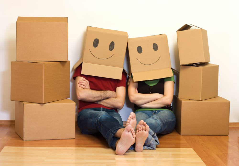 Couple sitting on floor, surrounded by boxes, with smiley-face boxes on their heads