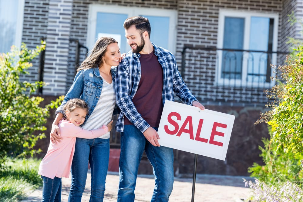 Young smiling family in front of house with SALE sign