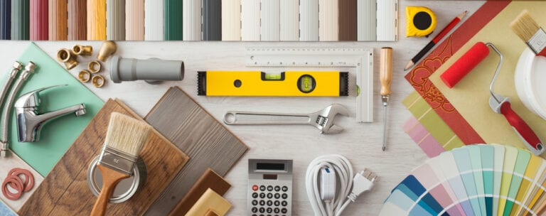Assortment of home renovation tools organized on white surface