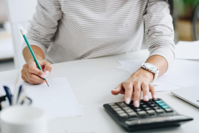 Close-up of woman using calculator, writing something down