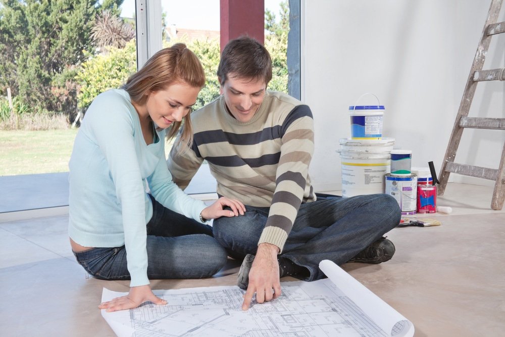 Young couple sitting on floor looking at renovation plans with excitement