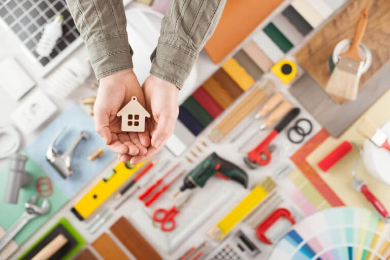 Remodeling supplies arranged on flat surface, hands holding small wood house model