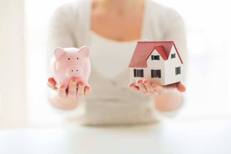 Woman holding a piggy bank in one hand, a small house model in the other