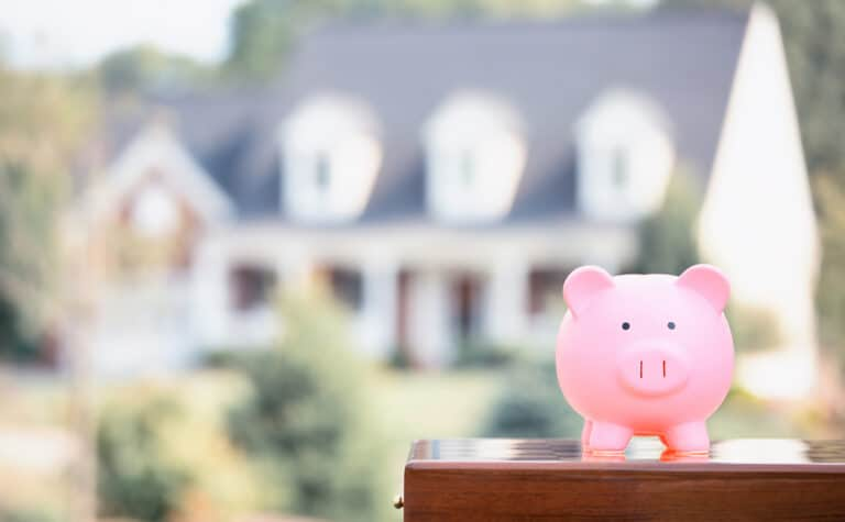 Pink piggybank close-up with house in the background