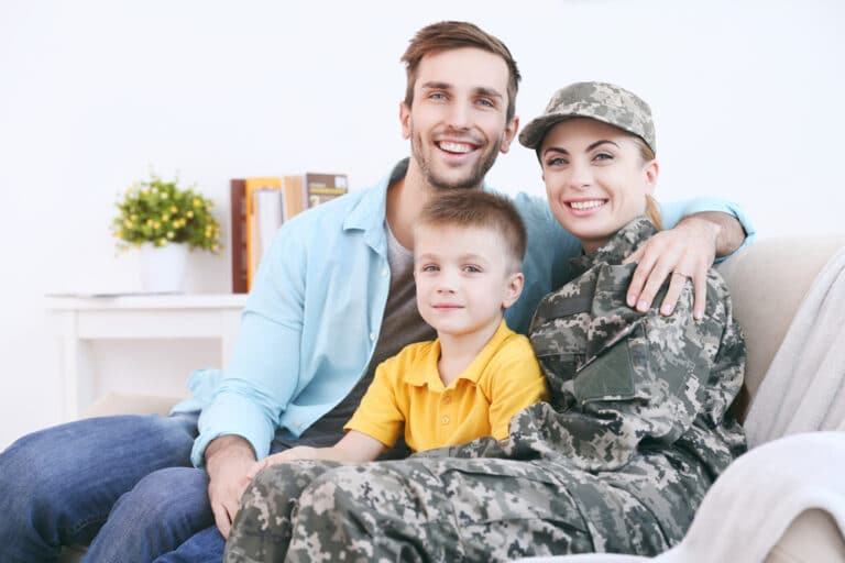 Smiling young father, mother wearing military uniform, and child on couch