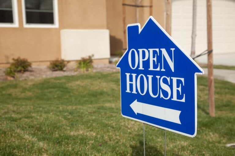 Close-up of open house sign in front of house