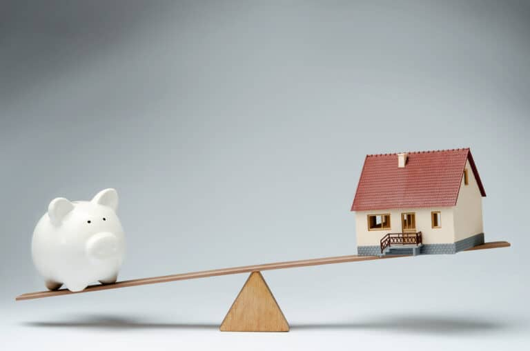 Balance scale with piggy bank and house model