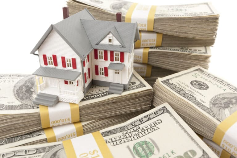Small house model on stacks of dollars