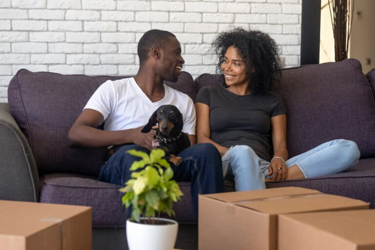 Young smiling couple and dog on couch, moving boxes in front