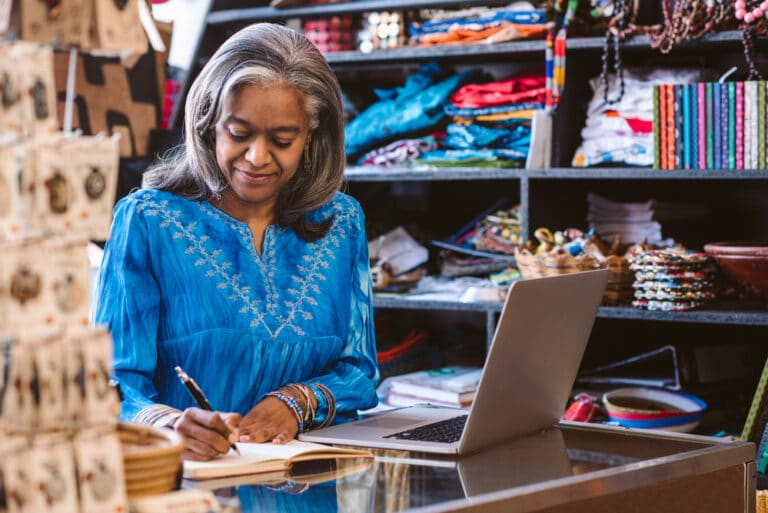 Female shop owner writing in notebook and looking at laptop