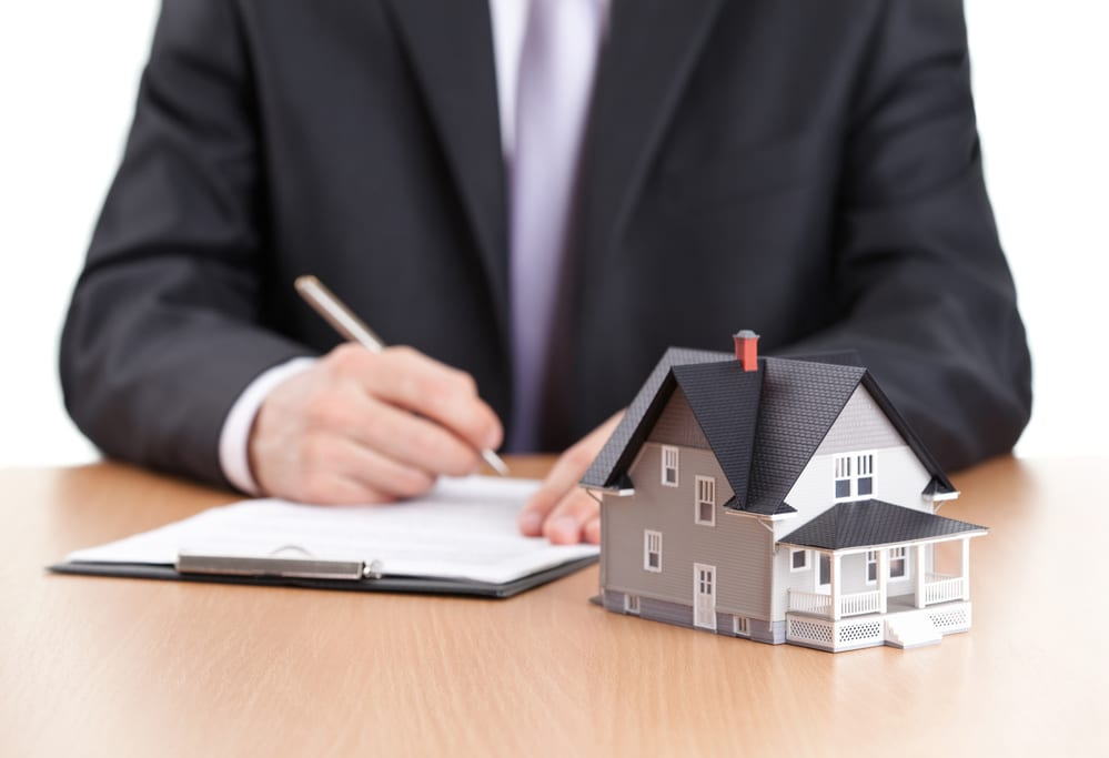 Man in suit writing on desk, tiny house model