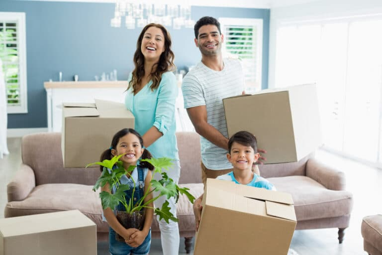 Smiling family standing in new living room, holding moving boxes and plant